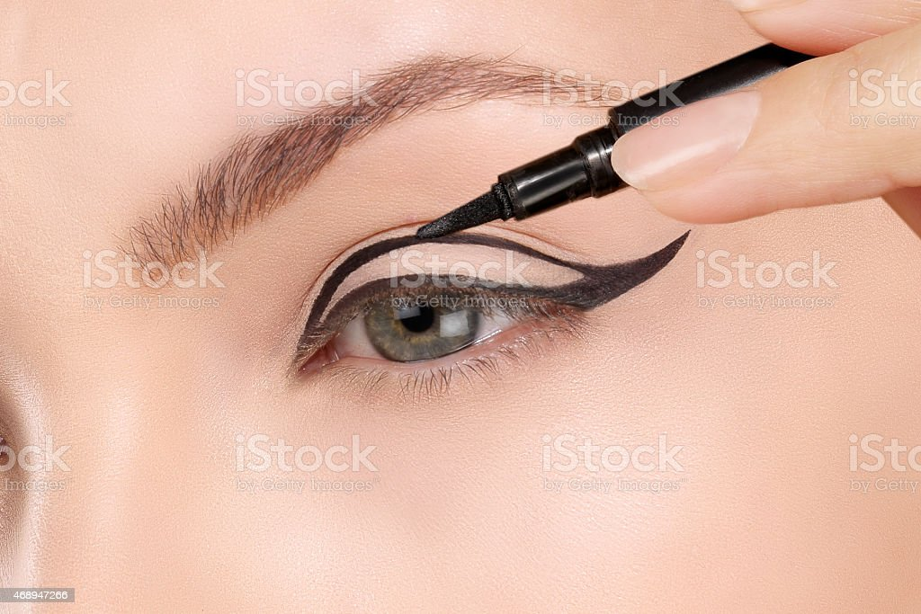 Beautiful model applying foundation with a brush stock photo