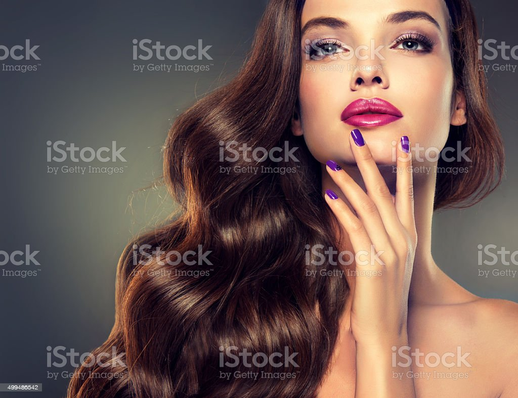Beautiful model brunette with long curled hair. stock photo
