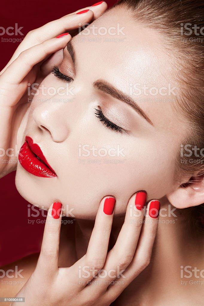 Beautiful model closeup beauty. Red manicured nails and lips. stock photo