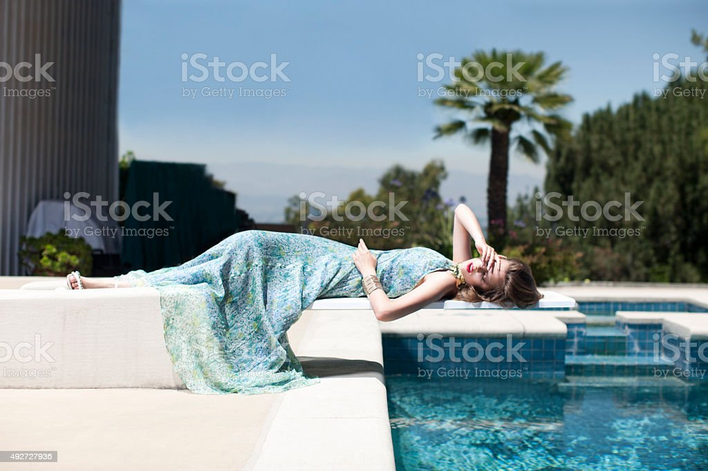 Beautiful Model in Dress Laying on Diving Board By Pool stock photo