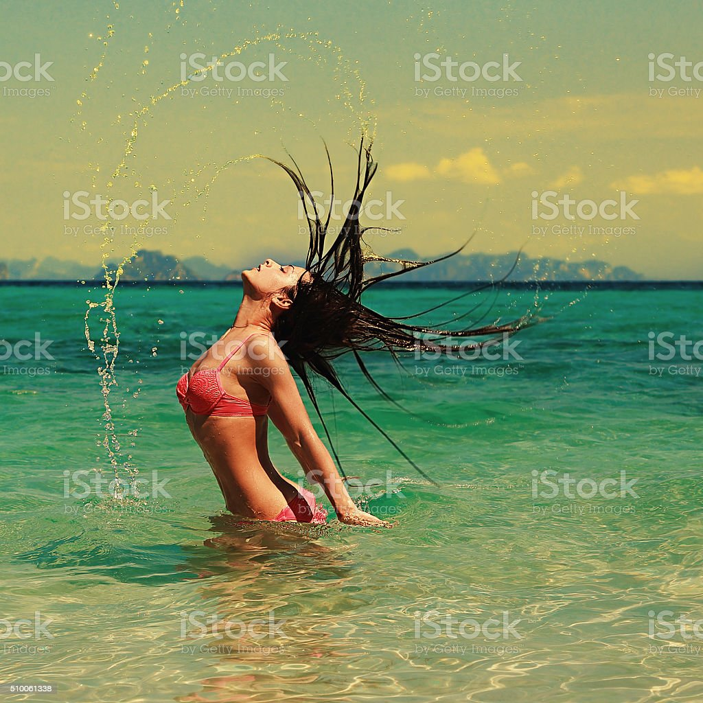 Beautiful model woman splashing her hair in turquoise azure wate stock photo