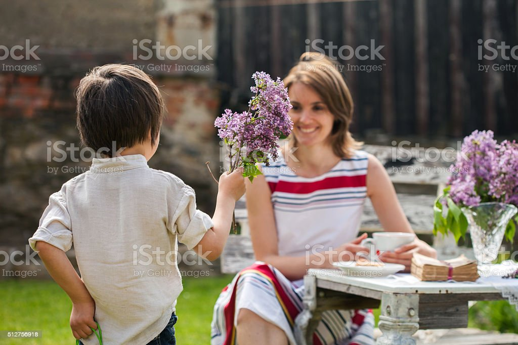 Beautiful mom, having coffee in a backyard stock photo