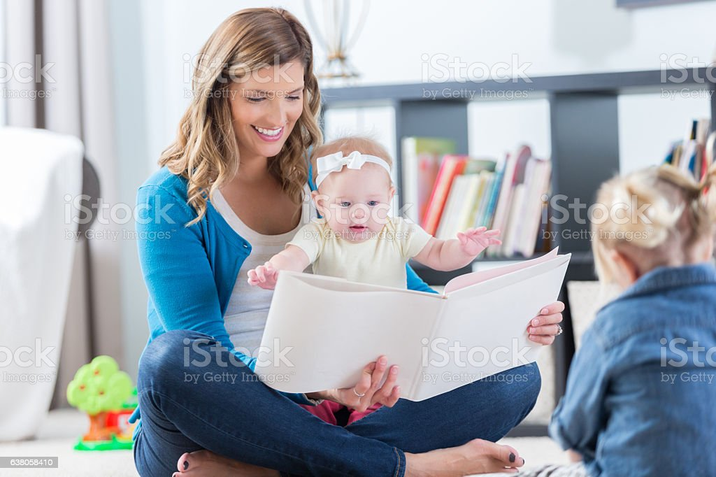 Beautiful mom reads to daughters stock photo