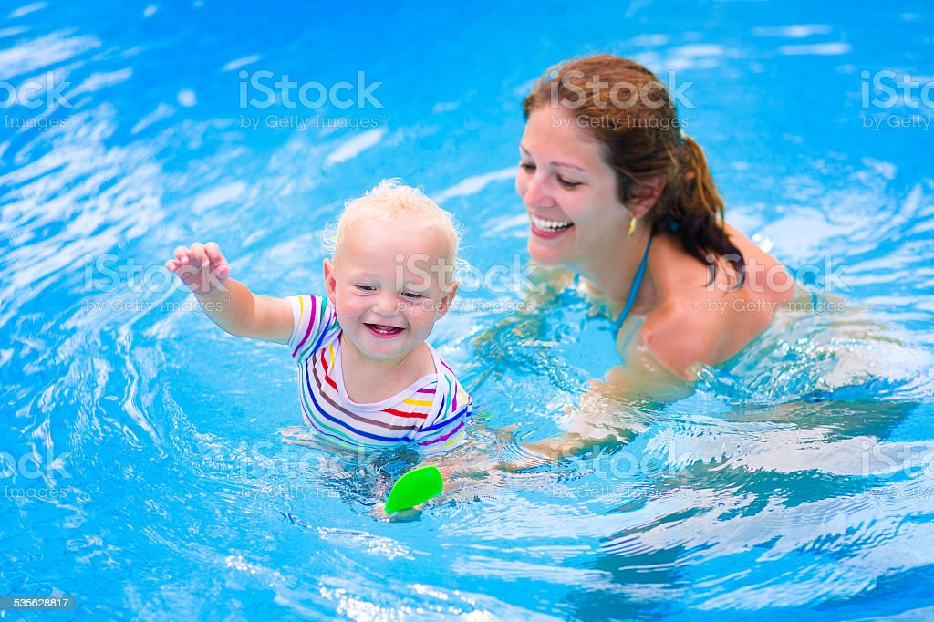 Beautiful mother and baby in swiming pool stock photo