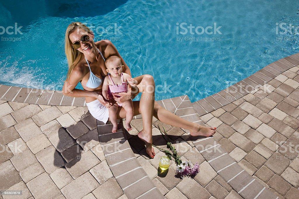 Hermosa Madre y bebé jugando con piscina de vacaciones foto de stock libre de derechos