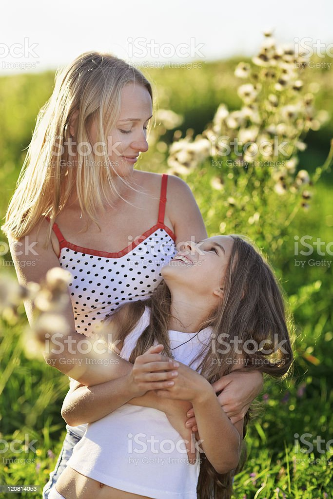 Beautiful mother and daughter family playing on meadow royalty-free stock photo