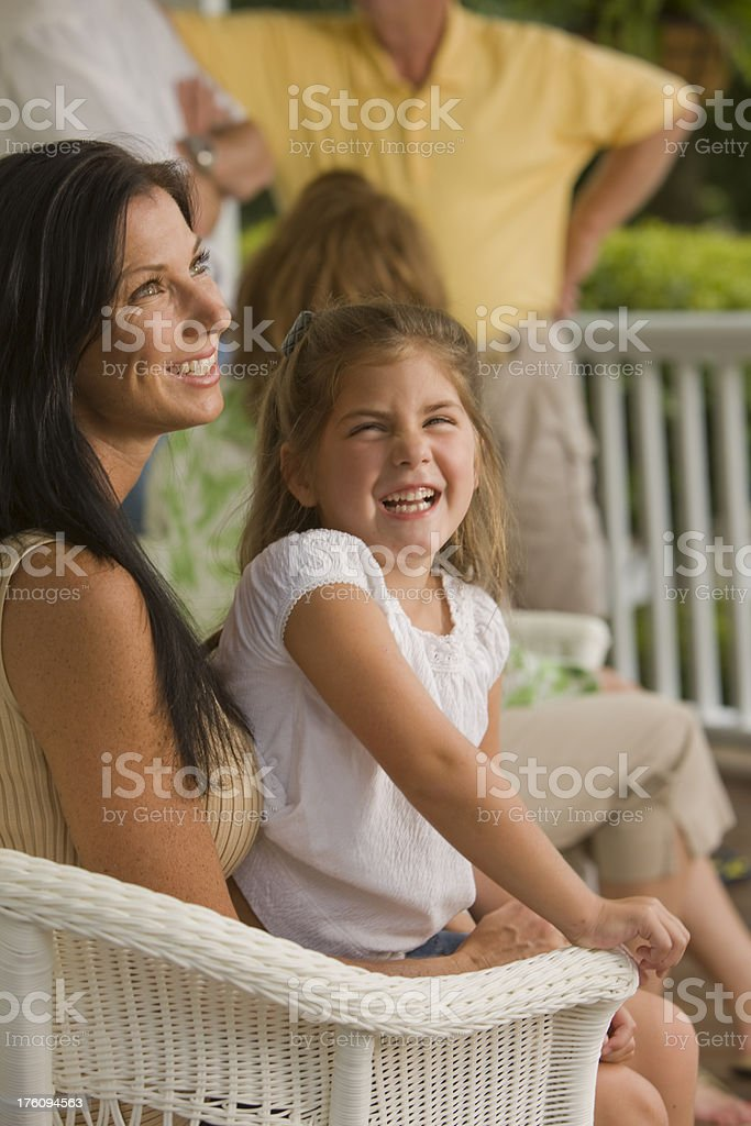 Beautiful mother and daughter laughing at a family reunion stock photo