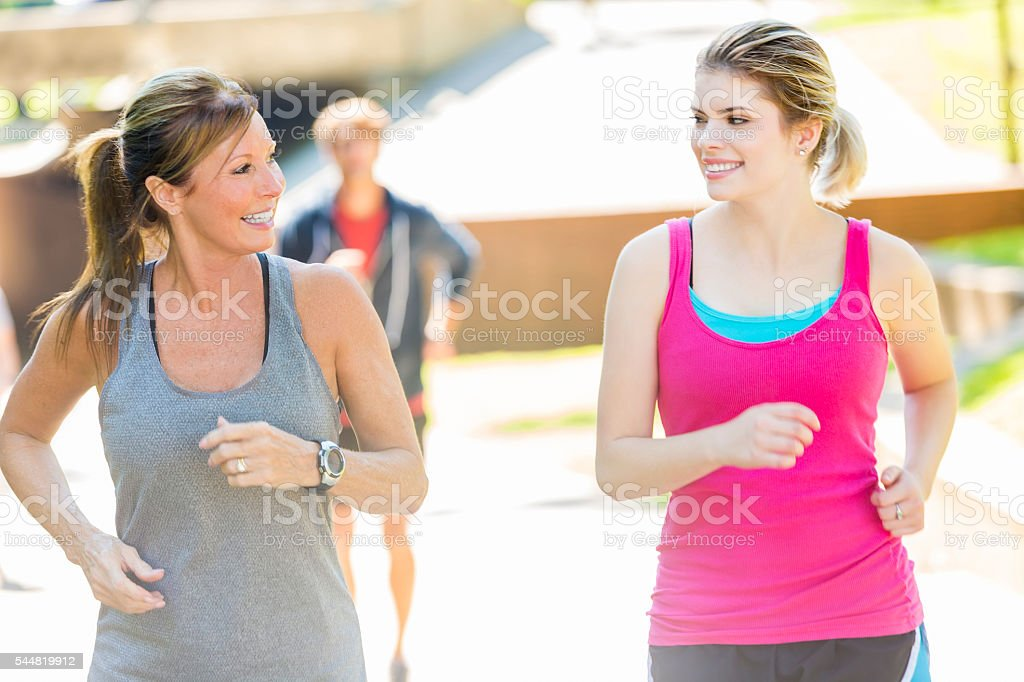 Beautiful mother and daughter running together in a park stock photo