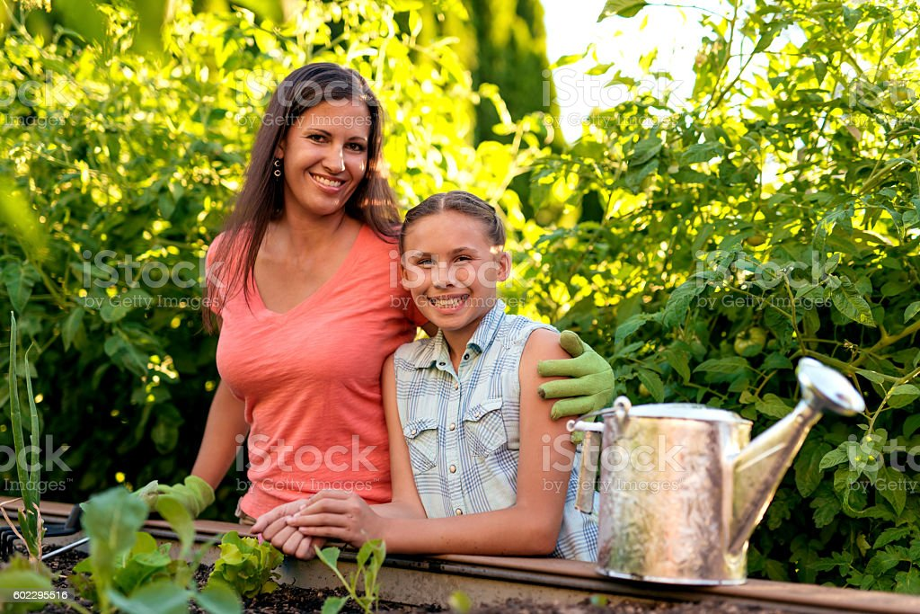 Beautiful mother and daughter smiling in front of their garden stock photo