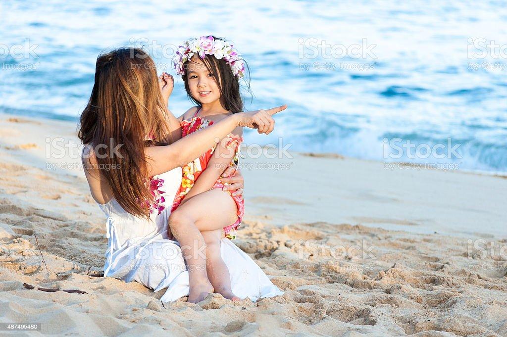 Beautiful mother and daughter wearing Lei on Hawaiian beach stock photo