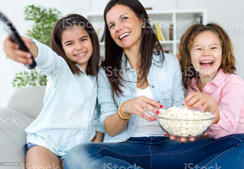Beautiful mother and her daughters eating popcorns at home. stock photo