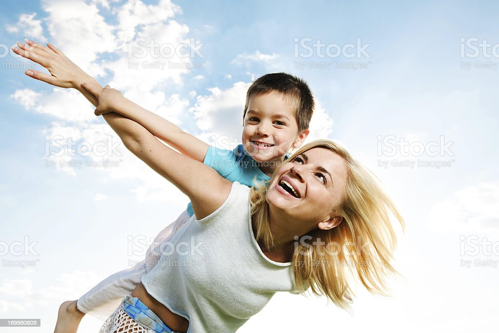 Beautiful mother giving her son a piggyback ride. royalty-free stock photo