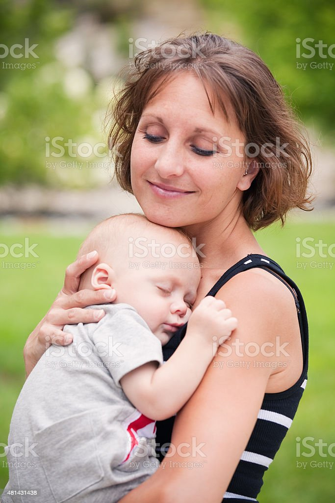 Beautiful Mother Holding Her Sleeping Baby Boy stock photo
