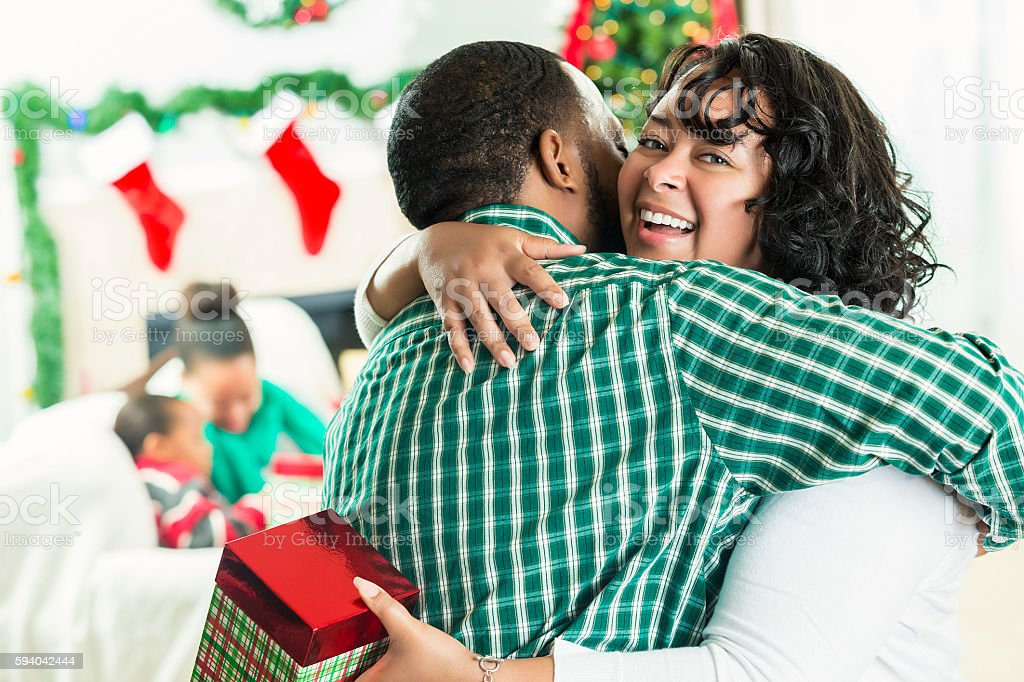Beautiful mother hugs husband on Christmas day stock photo