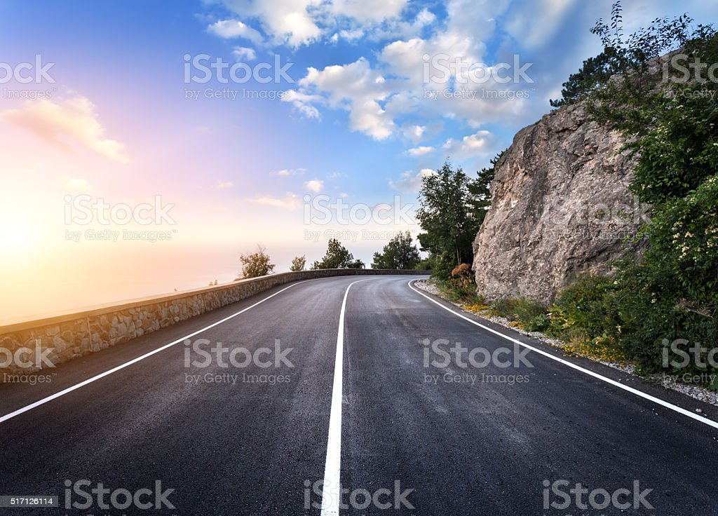 Beautiful mountain asphalt road with rocks, blue sky at sunset stock photo