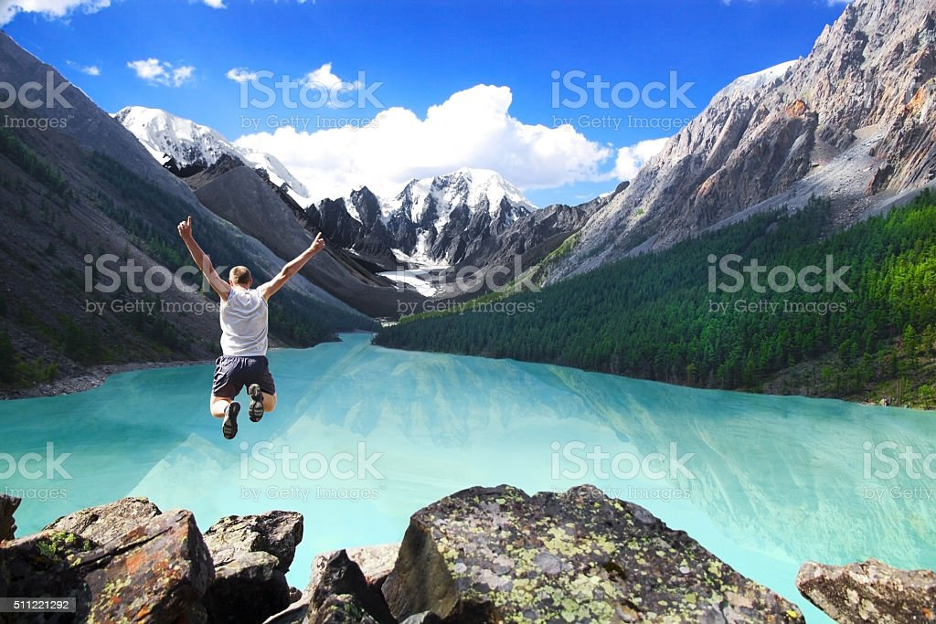 Beautiful mountain landscape with the lake and jumping man stock photo