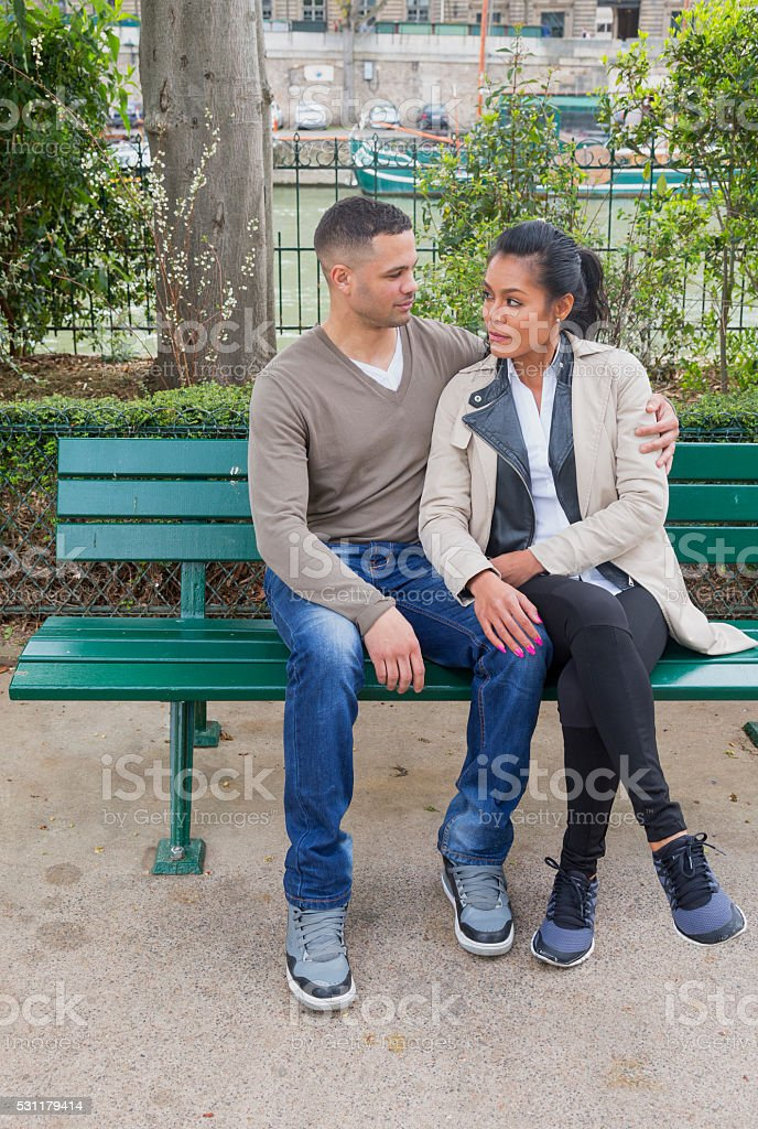 Beautiful multiethnic couple on a bench. Tender moment. Paris spring. stock photo