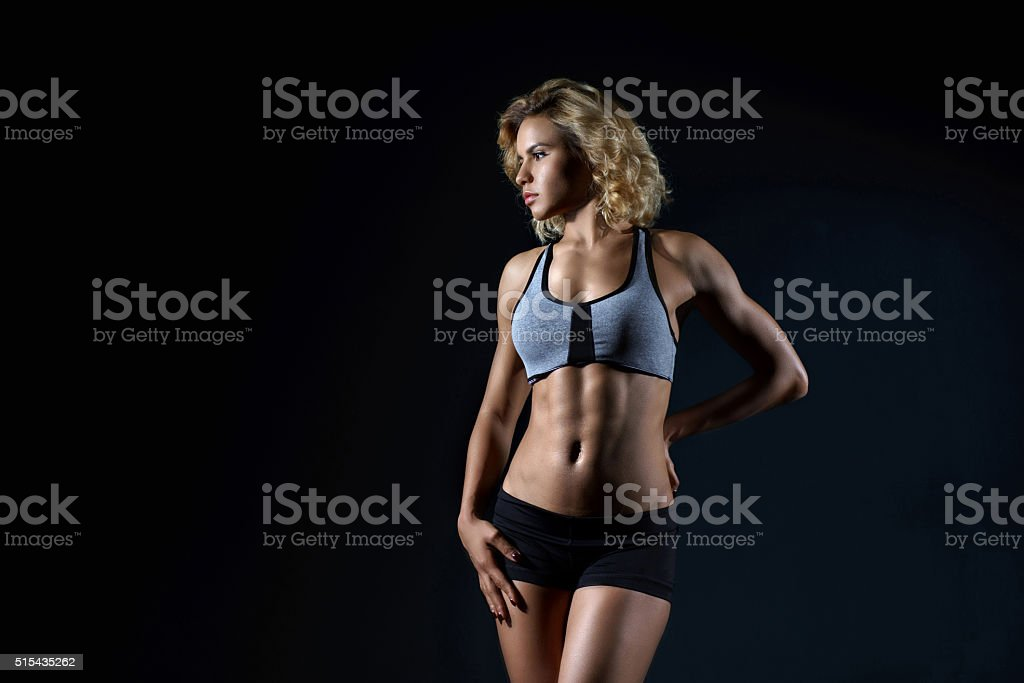 Beautiful muscular woman doing exercise  on a gray background stock photo