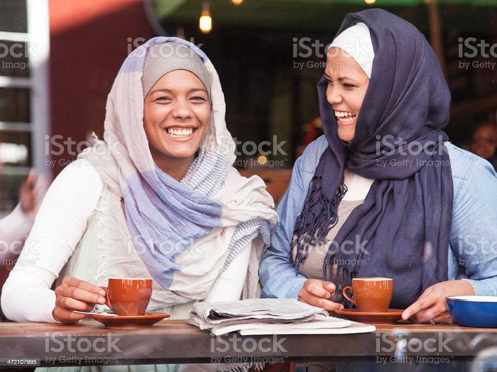 Beautiful muslim women laughing while having a cup of coffee. stock photo