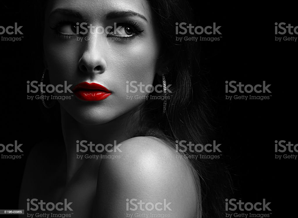 Beautiful mysterious woman in darkness looking dramatic with red lips stock photo