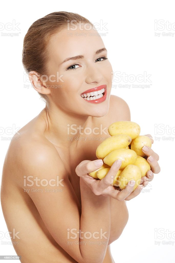 Beautiful naked caucasian woman is holding fresh, raw potatoes. royalty-free stock photo