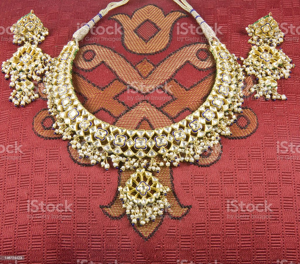 Beautiful Necklace and Earrings Display on Red Patterned Cloth royalty-free stock photo