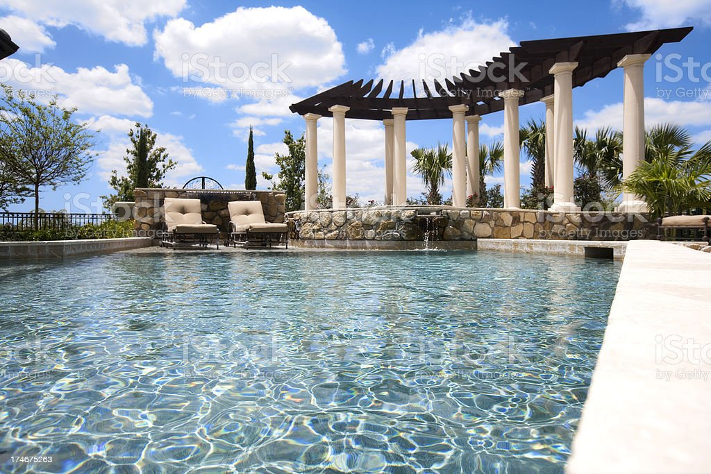 Beautiful new pool and firepit colums gazibo chairs water sky royalty-free stock photo