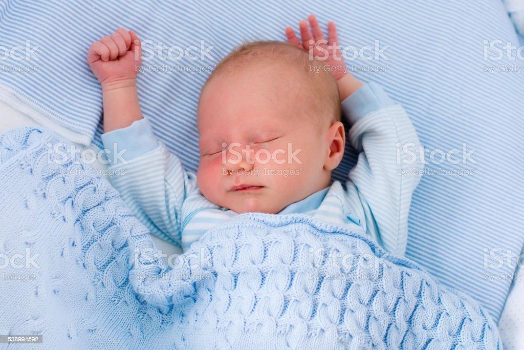 Beautiful newborn baby boy in white bassinet stock photo