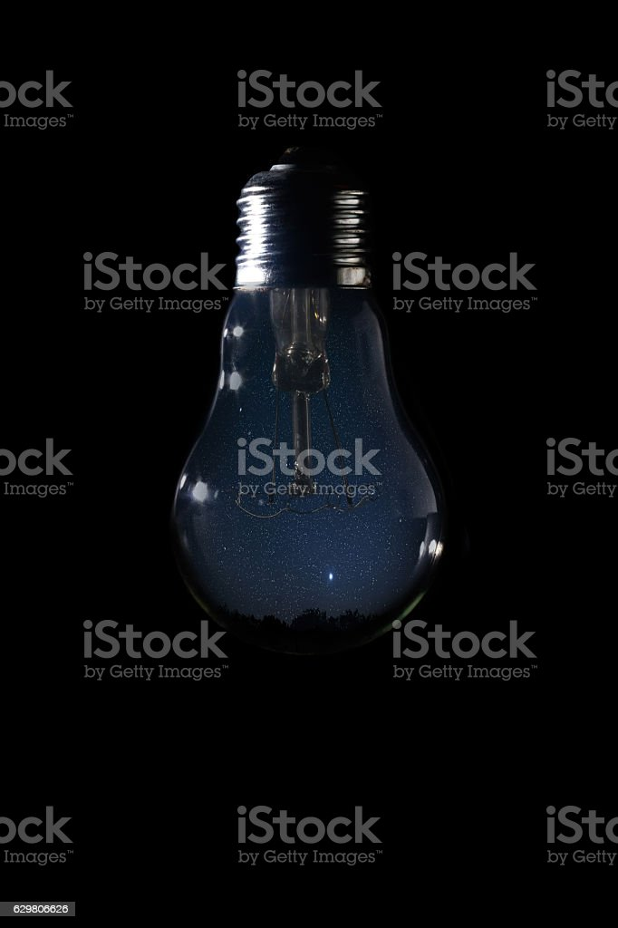 Beautiful night sky inside of light bulb on dark background stock photo