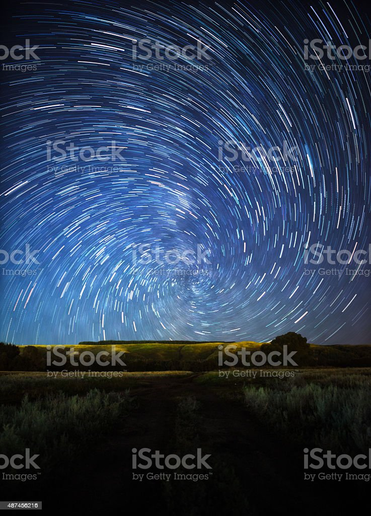 beautiful night sky, spiral star trails and the forest stock photo