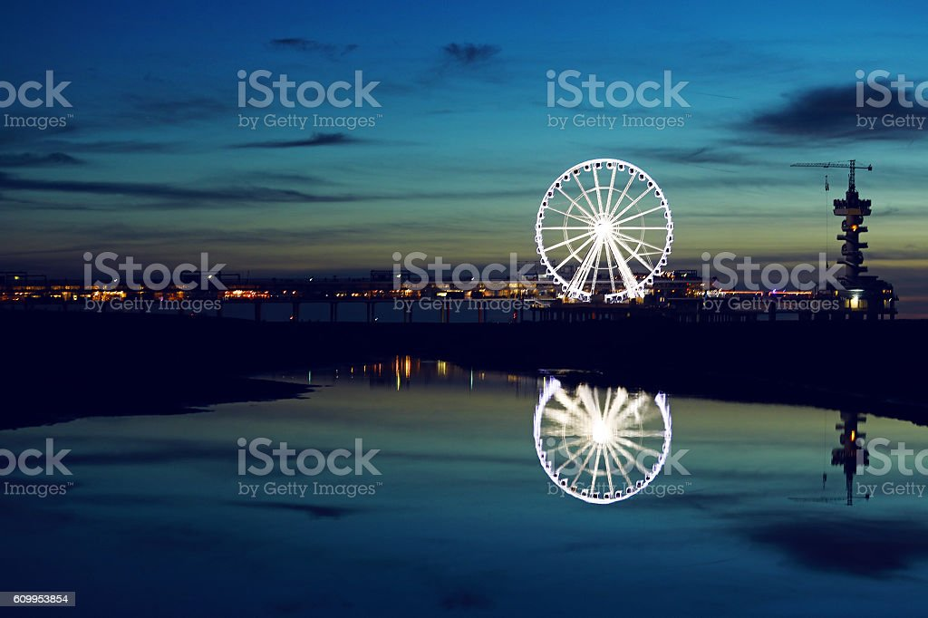Beautiful night time view of seaside pier and ferris wheel stock photo