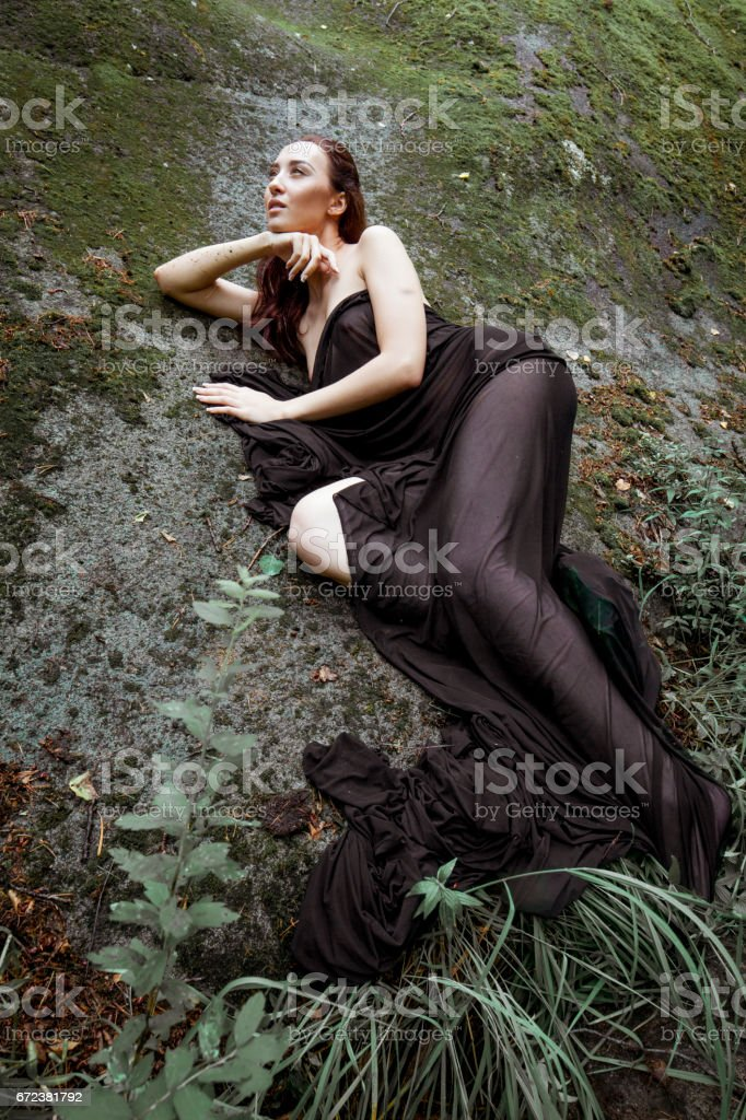 beautiful nude girl under the black cloth in the nature landscape stock photo