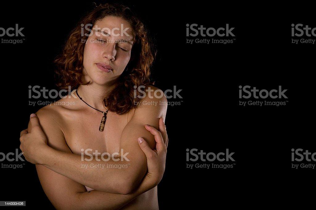 Beautiful Nude Woman Embracing Self on Black Background royalty-free stock photo
