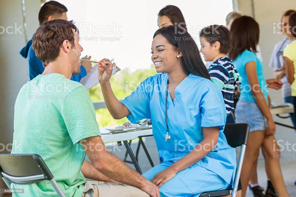 Beautiful nurse doing a health examination for a man stock photo