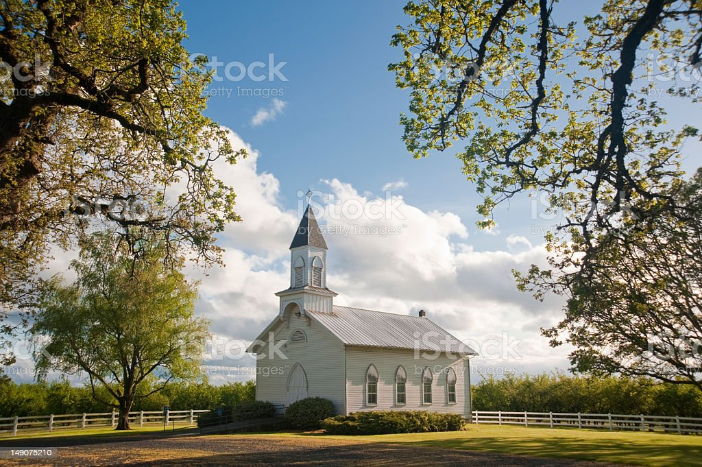 A beautiful old white rural Church in a field stock photo