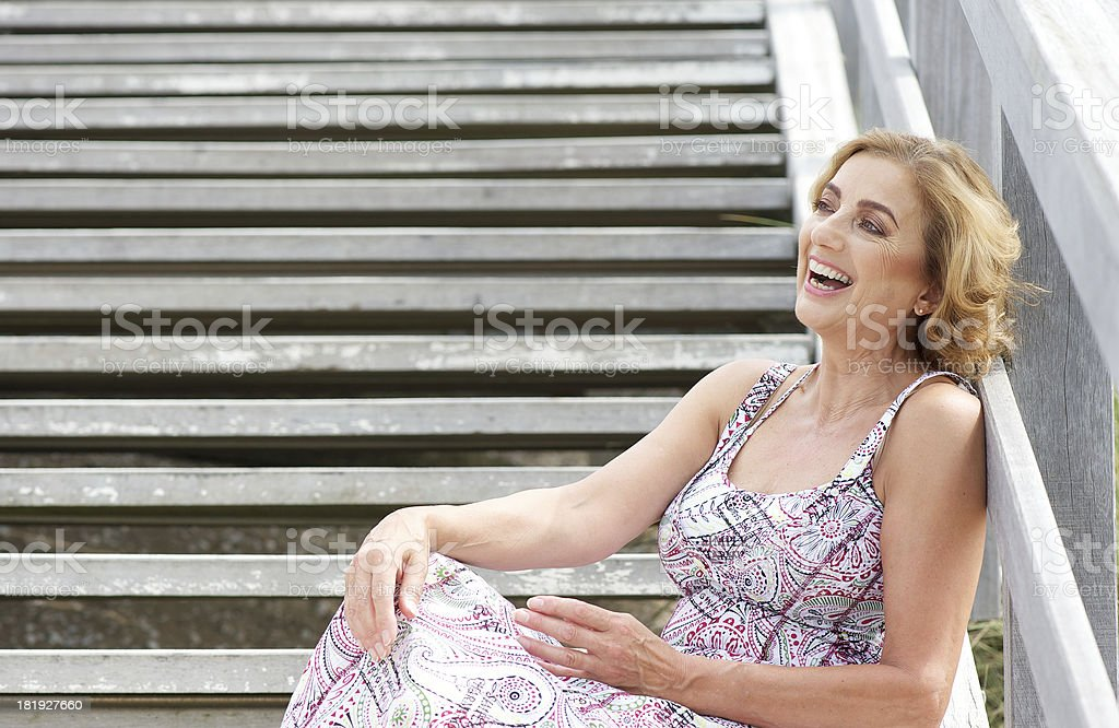Beautiful older woman sitting on stairs and laughing outdoors royalty-free stock photo