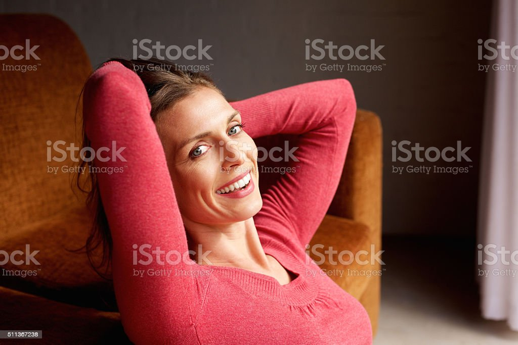 Beautiful older woman smiling with hands behind head stock photo