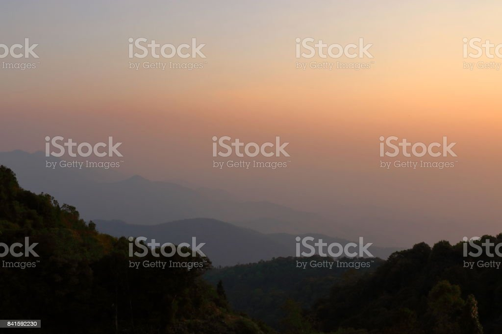 Beautiful orange and yellow sunset and layers of silhouettes mountain in Chiang Mai , Thailand stock photo