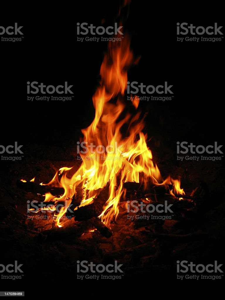 Beautiful orange flames from a campfire in pure darkness royalty-free stock photo