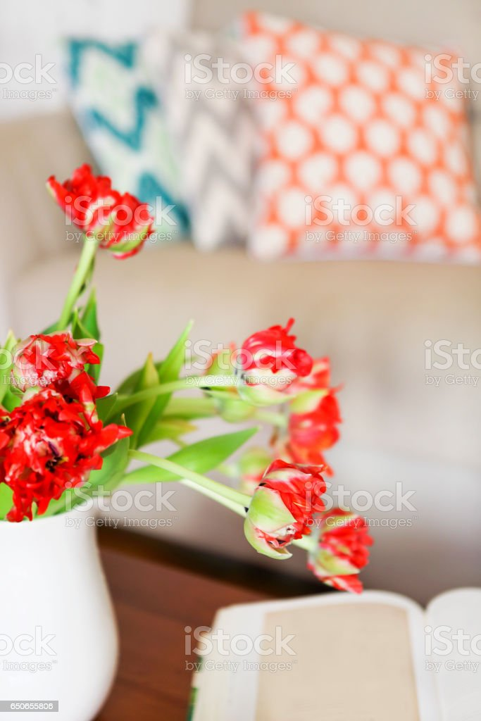Beautiful orange tulips bouquet on wooden table in the living room stock photo