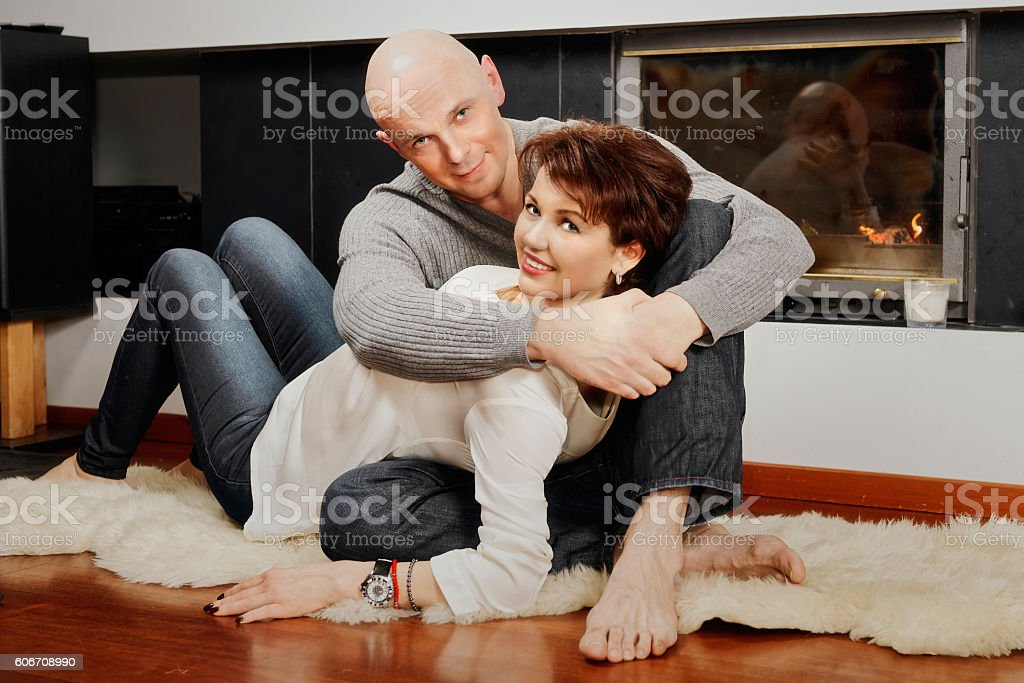 Beautiful pair sitting on fur carpet near fireplace stock photo