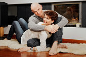 Beautiful pair sitting on fur carpet near fireplace