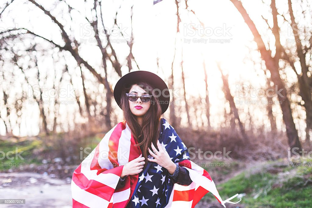 Beautiful patriotic young woman with the American flag stock photo