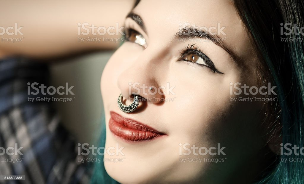 Beautiful pierced teenager looking at the light stock photo