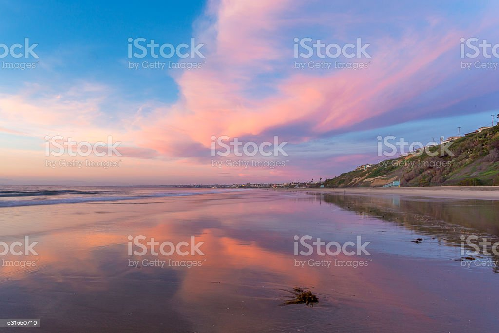 Beautiful Pink Clouds at Sunset on Beach stock photo