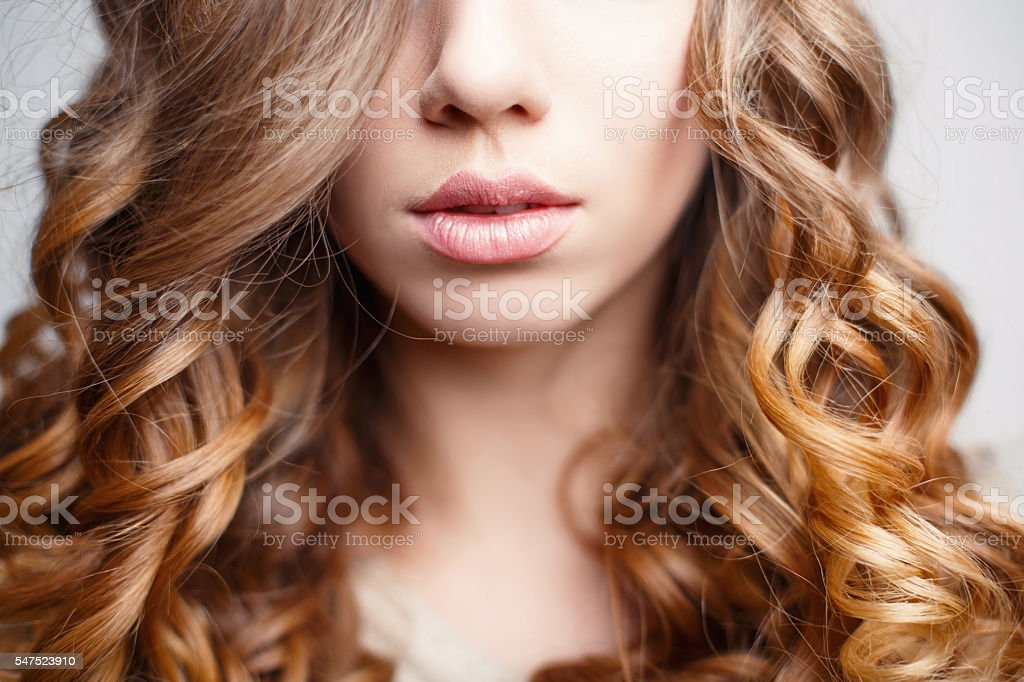 Beautiful pink lips close-up. Girl with curly hair stock photo