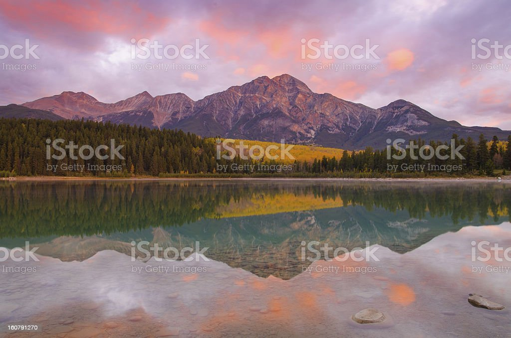 Beautiful pink sunrise by the mountains and lake stock photo