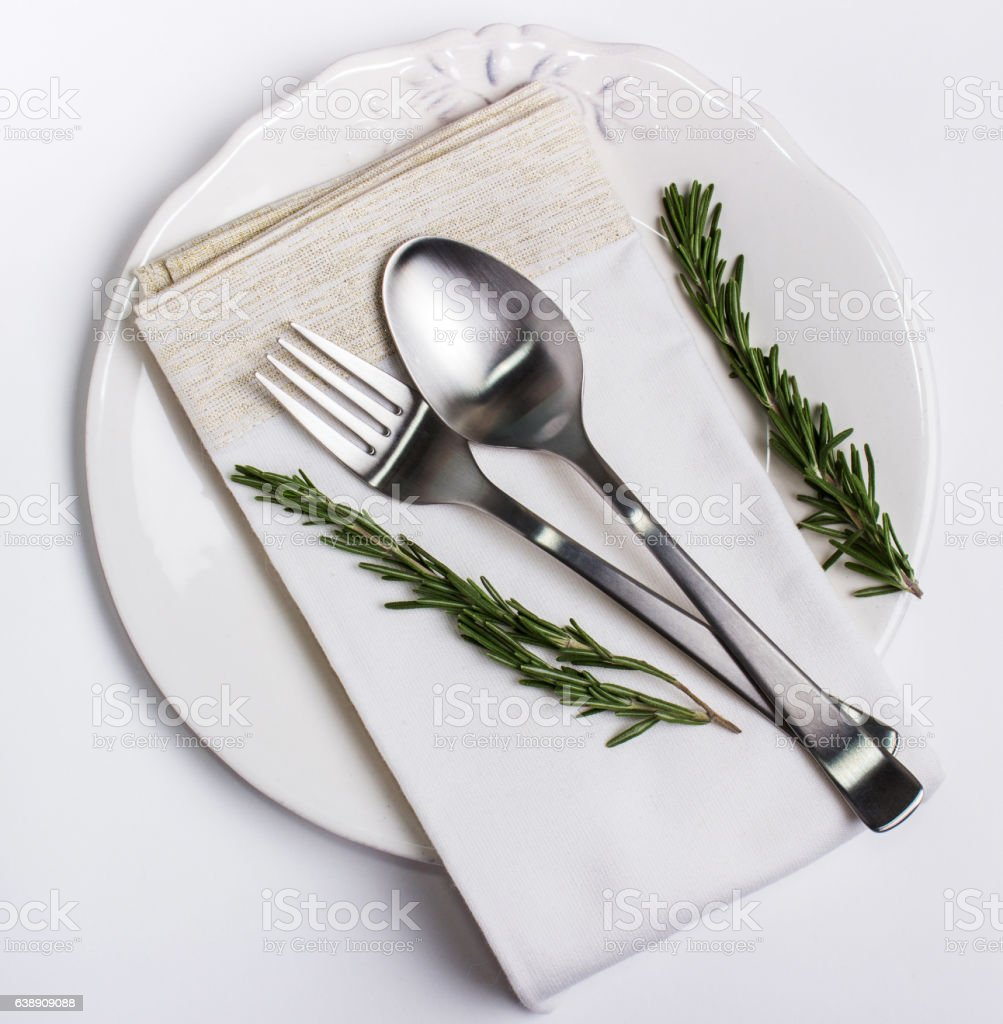Beautiful Plate, cutlery on a napkin, with rosemary stock photo