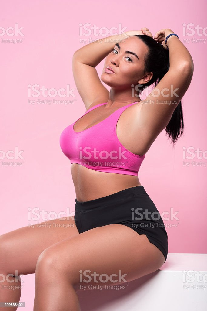 Beautiful plump woman sitting against pink background stock photo