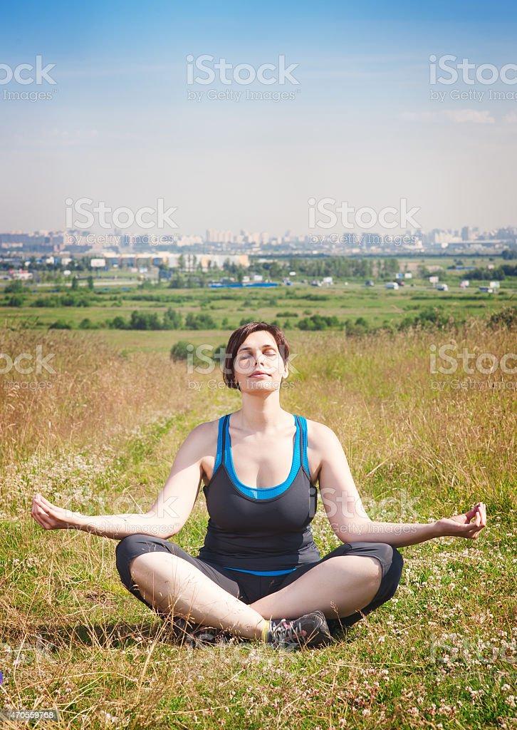 Beautiful plus size woman doing yoga outdoor stock photo